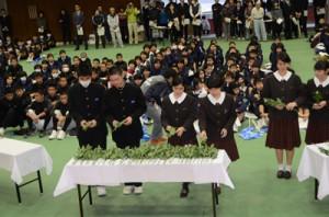泉芳朗に敬意を払い、献花する生徒ら=25日、奄美市