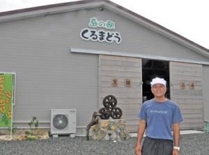 オープンした「島の駅くるまどう」と鬼塚社長=22日、与論町麦屋