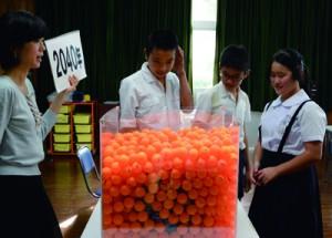 二酸化炭素に見立てたピンポン玉が地球を覆い温暖化する仕組みを紹介した植木さん(左)=9日、住用小学校