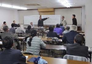 ポンカンやタンカンの買い上げ単価や廃棄について説明する担当者ら=6日、奄美市役所