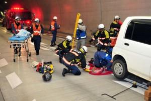 トンネル事故を想定し、迅速な通報や負傷者救助など、関係機関の連携を確認した防災訓練=13日、網野子トンネル(瀬戸内町側)