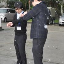雪を観測する職員ら=24日午後3時57分ごろ、奄美市の名瀬測候所