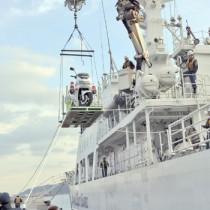 海保職員によって巡視船に積み込まれる白バイ=27日、名瀬港観光船バース