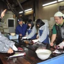 釣り上げたカツオやキハダマグロをさばく須磨友が丘高校の生徒=20日、奄美市名瀬