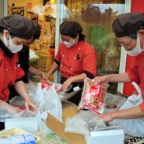 アンケート抽選の当選者に発送する地場産セットの箱詰め作業=22日、龍郷町
