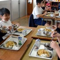マダ汁や島豚パパイア丼などの郷土料理を給食で楽しんだ児童たち=18日、奄美市の名瀬小学校