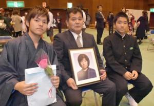 雅恵さんの遺影を手に成人式に参列した稲井さん家族(左から啓大さん、均さん、駿君)=4日、瀬戸内町