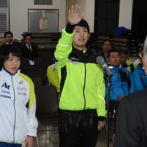 堂々と選手宣誓する(右から)岸田賢吾、平島美来の両選手=19日、大島支庁の奄美会館
