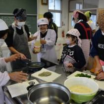 講師の手ほどきを受けながら油ぞうめんを作る崎原小中学校の児童、生徒たち=22日、奄美市の崎原小中学校