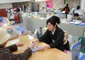 大島紬姿で接客に当たる女性職員=4日、奄美市