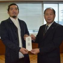 新築住宅助成金の目録を手にする吉見さん(左)と鎌田町長=2日、瀬戸内町役場