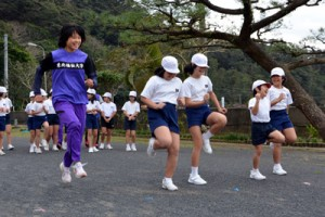 もも上げなどの基礎トレーニングを学生に教わった児童たち=22日、宇検村立田検小学校