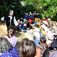 「世之主伝説」に熱心に聴き入る来場者=6日、和泊町の内城小学校