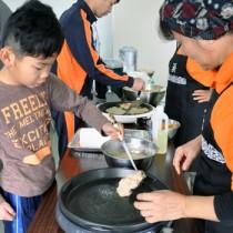 ジャガイモお焼き作りに挑戦する参加者=27日、和泊町の実験農場