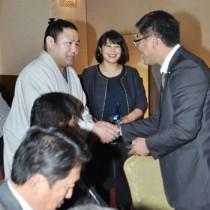 出席者にあいさつして回る里山関(左)と妻の美菜さん(中央)=10日、奄美市名瀬
