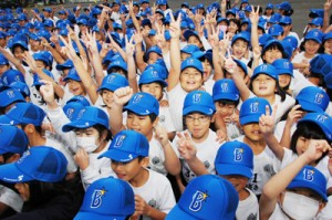 ベイスターズから届いた野球帽をかぶり笑顔の児童ら=3日、奄美市の朝日小学校