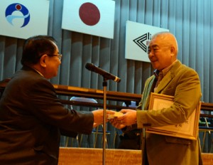 委嘱状と名刺を受け取る柳本さん(右)=28日、奄美市の小宿小学校体育館