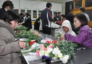 徳之島産のトルコギキョウを使ったフラワーアレンジメントに挑戦する参加者ら=16日、面縄中学校