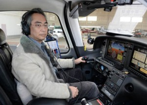 操縦席の川畑さん(上)。愛機の前で記念撮影する川畑さん(右から2人目)=2日、鹿児島空港