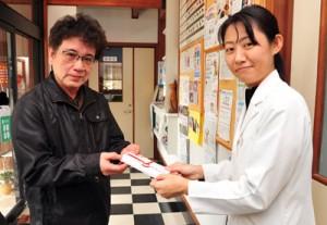 写真2枚(よことたて) よこ 徳之島で寄せられた募金を伊藤さん(右)に手渡す池村さん=4日、奄美市名瀬