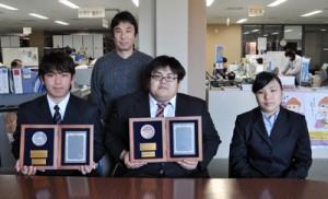 第26回ヤンマー学生懸賞論文・作文で入選した(左から)市山泰大さん、東優志さん、松木遥香さん、後ろは指導に当たった松岡尚二教授=8日、日置市の県立農業大学校