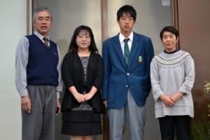 与論高校を卒業した奥野君親子(中央)と星砂荘の永井さん夫妻=与論町