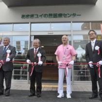 テープカットをして医療センターの開院を祝う(右から2人目)寺倉宏嗣院長ら関係者=31日、天城町