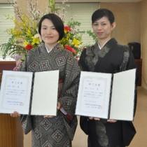 修了証書を受け取り、さらなる研さんを誓った丸山さん(右)と金田さん=17日、奄美市名瀬の紬会館