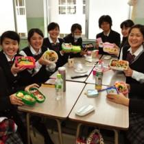 自分で用意した弁当を手に笑顔の生徒たち=18日、笠利町の大島北高校