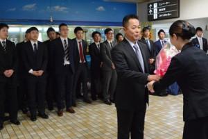 歓迎の花束を受け取る七十七銀行硬式野球部の上野監督ら一行=3日、奄美空港