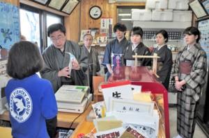 水産物販売所を訪問し、商品の宣伝方法などについて職員らと共に考えた学生ら=奄美市笠利町