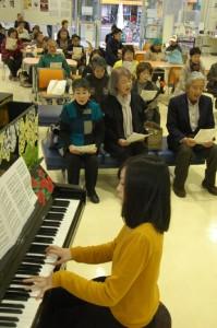 ピアノ伴奏に合わせ祈りのハーモニーを響かせた市民ら=11日、奄美市名瀬