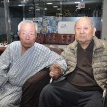 70年ぶりの再会を果たした久保さん(右)と高國さん=15日夜、奄美市名瀬