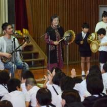 特別授業で、児童と一緒に島唄を披露する中孝介さん(左)=9日、田検小学校体育館