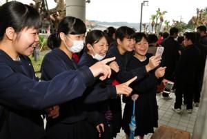 自分の番号を確認し、友人と喜び合う受験生たち=16日、奄美市名瀬の県立大島高校