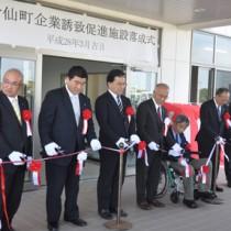 工場の落成式でテープカットを行う日本マルコの小板橋博行社長(右から3人目)と大久保明町長(同4人目)ら=29日、伊仙町