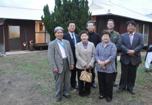 空き家を改修した「島宿 母間・本家」とプロジェクトを実施した藤﨑はつみ代表取締役(前列右)=24日、徳之島町
