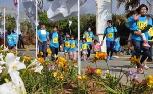 沿道の花を楽しみながらゴールを目指す参加者=13日、和泊町の笠石海浜公園