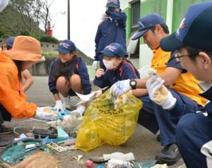 奄美海保の職員と漂着ごみ調査で集めたごみを分類する生徒たち=28日、龍郷町の嘉渡海岸