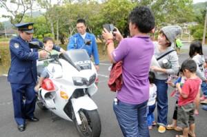 白バイの乗車体験を楽しむ参加者=3日、宇検村体育館駐車場