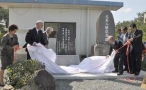 大原入植50周年の節目に移転、新設された2つの記念碑を除幕する関係者ら=15日、徳之島町