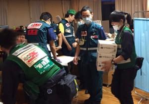 近隣病院から移された入院患者のベッドが並ぶデイケア室で活動するDMAT隊員=17日、熊本市の東病院(中村健太郎医師提供)