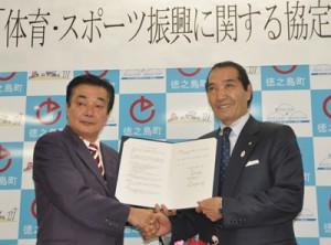 協定を締結して握手を交わす高岡秀規町長(左)と松浪健四郎理事長=13日、徳之島町