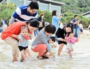 健やかな成長を祈って海水に子どもの足を浸す母親たち=9日、奄美市名瀬の大浜海浜公園