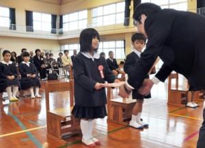 愛島校長から教科書を受け取り、笑顔の新入生=6日、大和村の今里小学校
