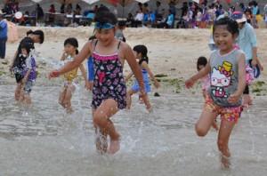 海開きで、水しぶきを上げながら海へと向かう子どもたち=24日、和泊町のワンジョビーチ