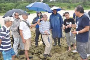 土盛海岸であった微生物岩の現地説明会。中央が中森亨准教授=24日、奄美市笠利町