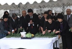 祭壇に献花して犠牲者のみ霊を慰める遺族ら=22日、徳之島町