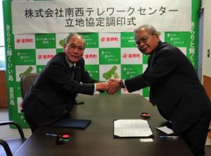 調印式で握手を交わす川島町長と南郷社長(左)と、開所式で業務のデモンストレーションを見学する出席者ら=5日、喜界町