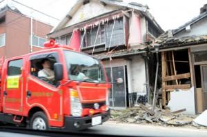 損壊した家屋の前を消防車が通る=18日午後5時50分ごろ、氷川町